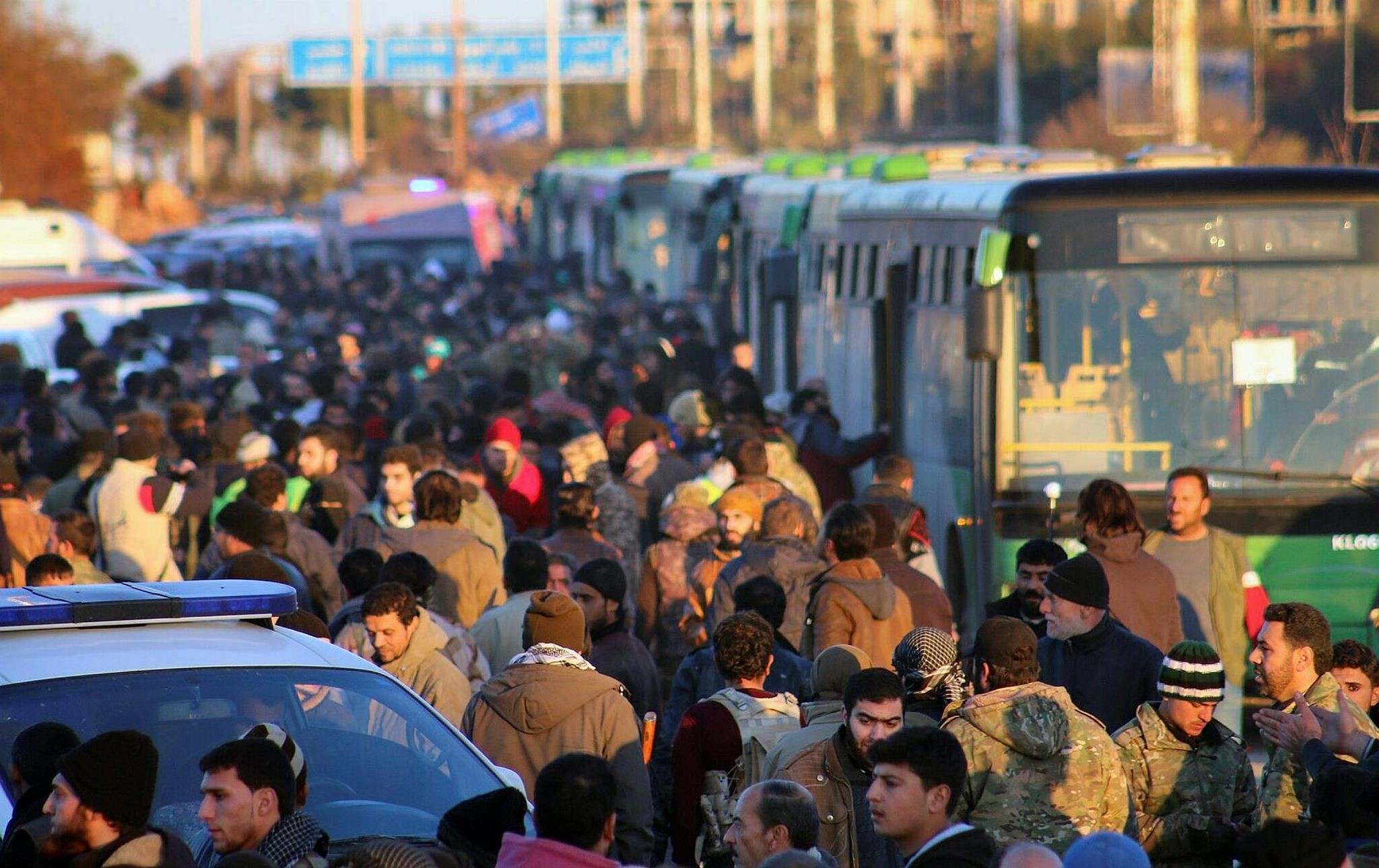 Residents gathered near green buses as they hold their belongings for evacuation from eastern Aleppo, Syria. (AP Photo)