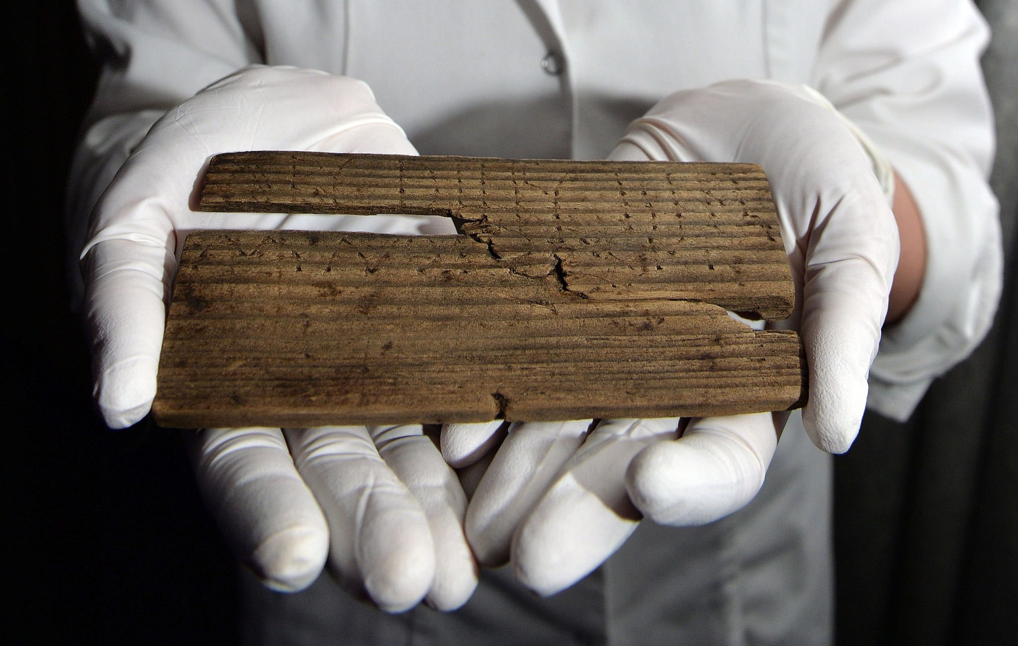 Luisa Duarte, a conservator for the Museum of London, holds a piece of wood with the Roman alphabet written on it in, in London, Wednesday, June 1, 2016 (AP Photo