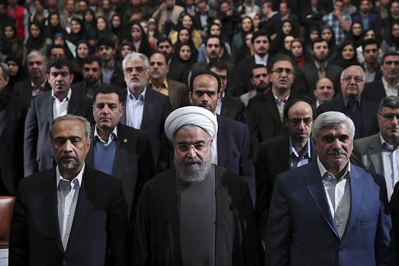 Iranian President Hassan Rouhani, center, listens to the national anthem at the start of a ceremony marking Student Day at Tehran University. Dec. 6, 2016. (AP Photo)