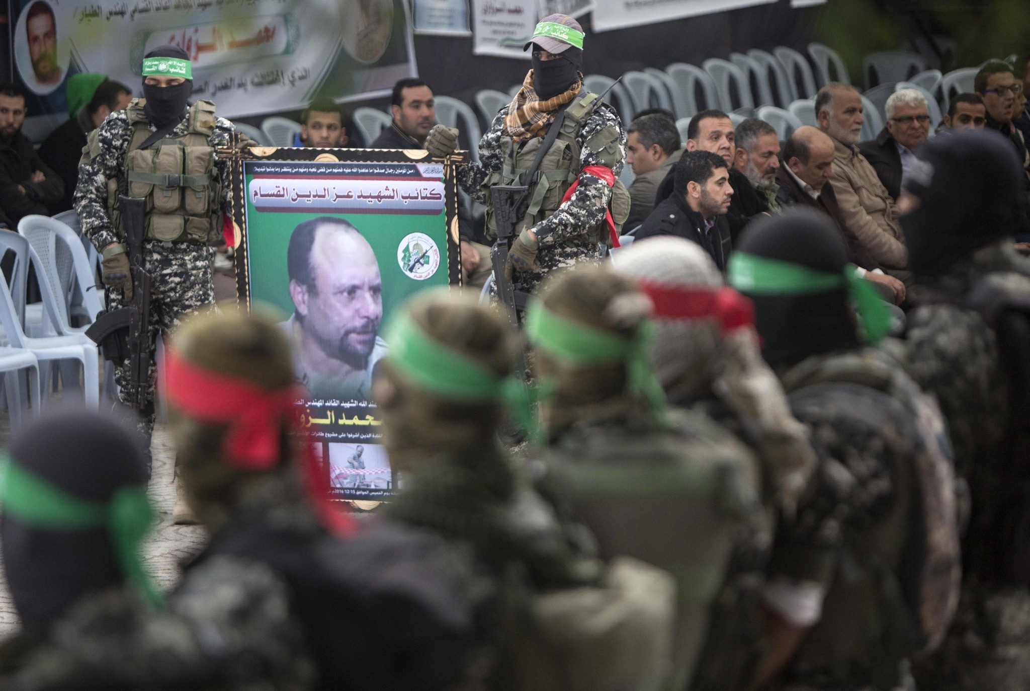 Members of the Ezzedine al-Qassam Brigades hold a banner bearing a portrait of one of their leaders, Mohamed Zaouari. (AFP Photo)