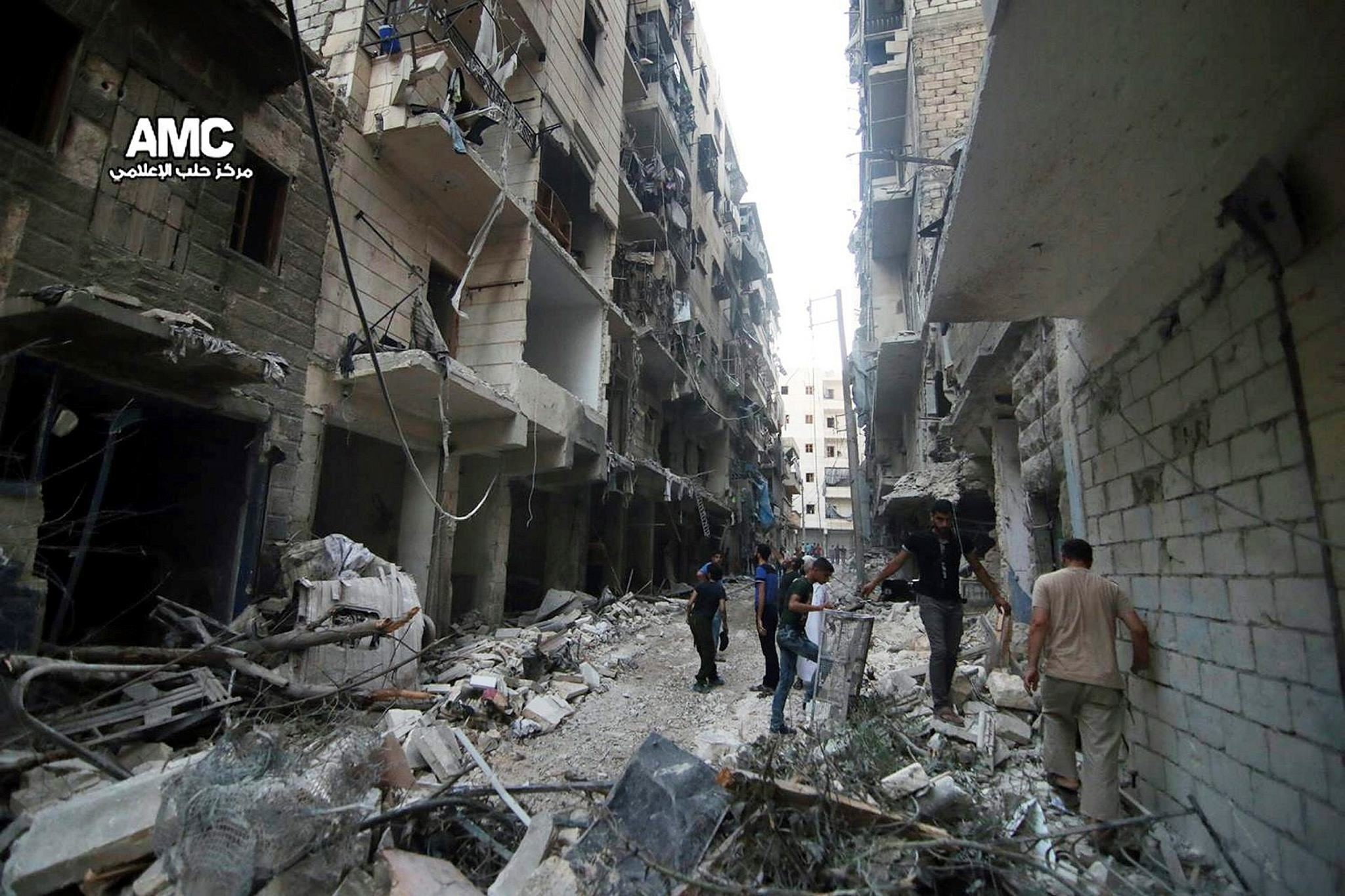 July. 29, 2016 photo, provided by the Syrian anti-government activist group Aleppo Media Center (AMC), shows Syrian citizens inspect damaged buildings after airstrikes hit Aleppo, Syria.