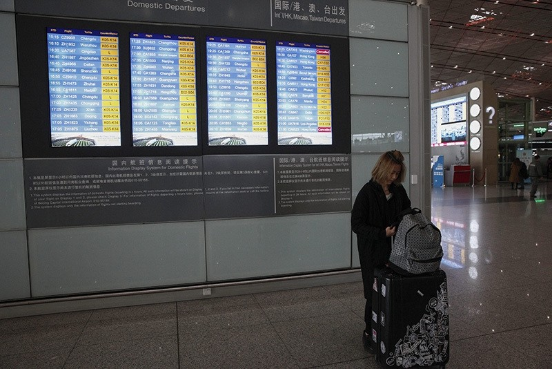 A woman attends to her luggage as flight details are posted on an electronic screen at the Beijing Capital International Airport in Beijing, China, Nov. 21, 2016. (EPA Photo)