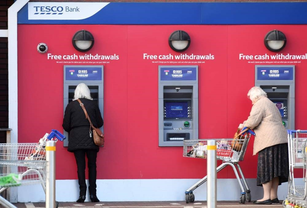 Customers use RBS branded automated teller machines (ATMs) at a Tesco Bank cash point, in Liverpool.