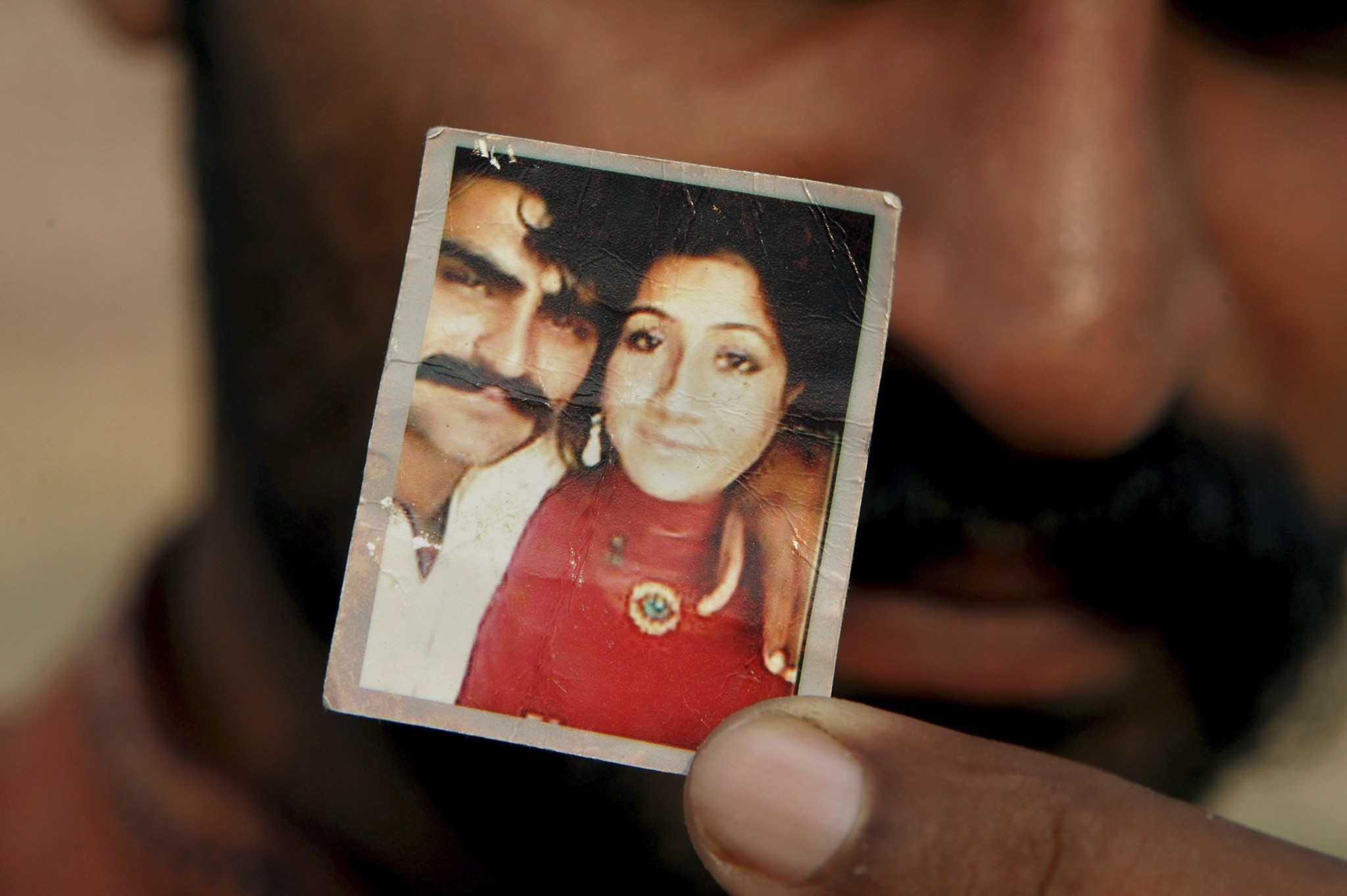 In this June 18, 2016 photo, Mohammed Tofeeq shows a picture with his wife Muqadas Tofeeq, who local police say was killed by her mother, in Butrawala village on the outskirts of Gujranwala, Pakistan. (AP Photo)