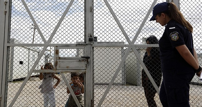 Children from Iraq stand behind the fence as a policewoman stands guard at Amygdaleza pre-departure center for refugees and migrants who are asking to return home, in Athens, Wednesday, Sept. 21, 2016 (AP Photo)