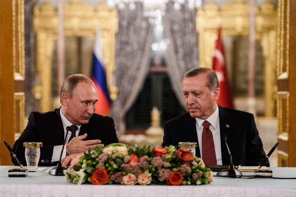Russian President Vladimir Putin speaking to President Recep Tayyip Erdogan as they attend a press conference in Istanbul.
