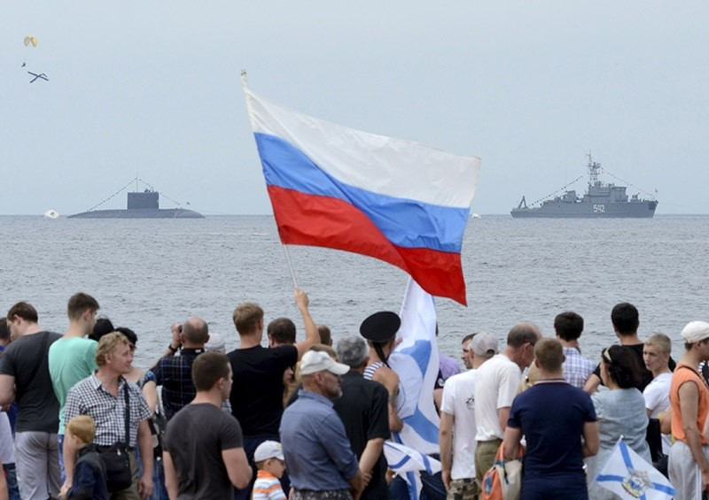 People gather to watch celebrations for Navy Day, with a Russian warship and a submarine seen in the background. July 2015. (Reuters Photo)