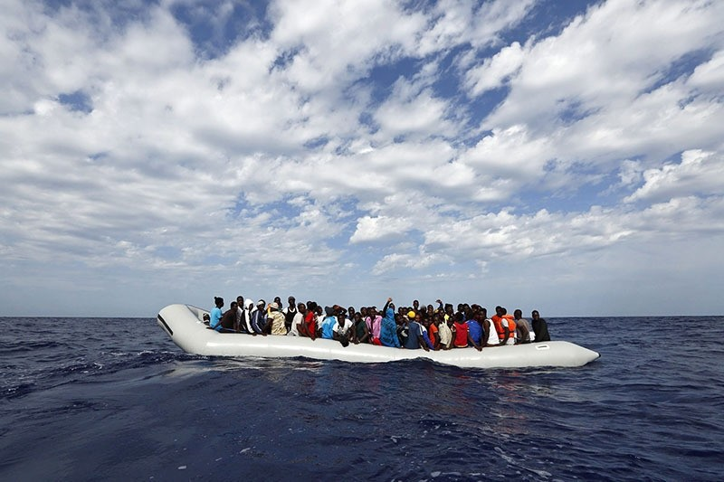 Refugees on a rubber raft waiting to board the 'Phoenix', a ship belonging to the Migrant Offshore Aid Station (MOAS), off the island of Lampedusa, Italy, 04 October 2014 (EPA)