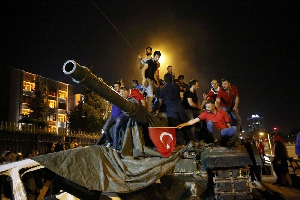 People stand on a Turkish army tank in Ankara, Turkey July 16, 2016.