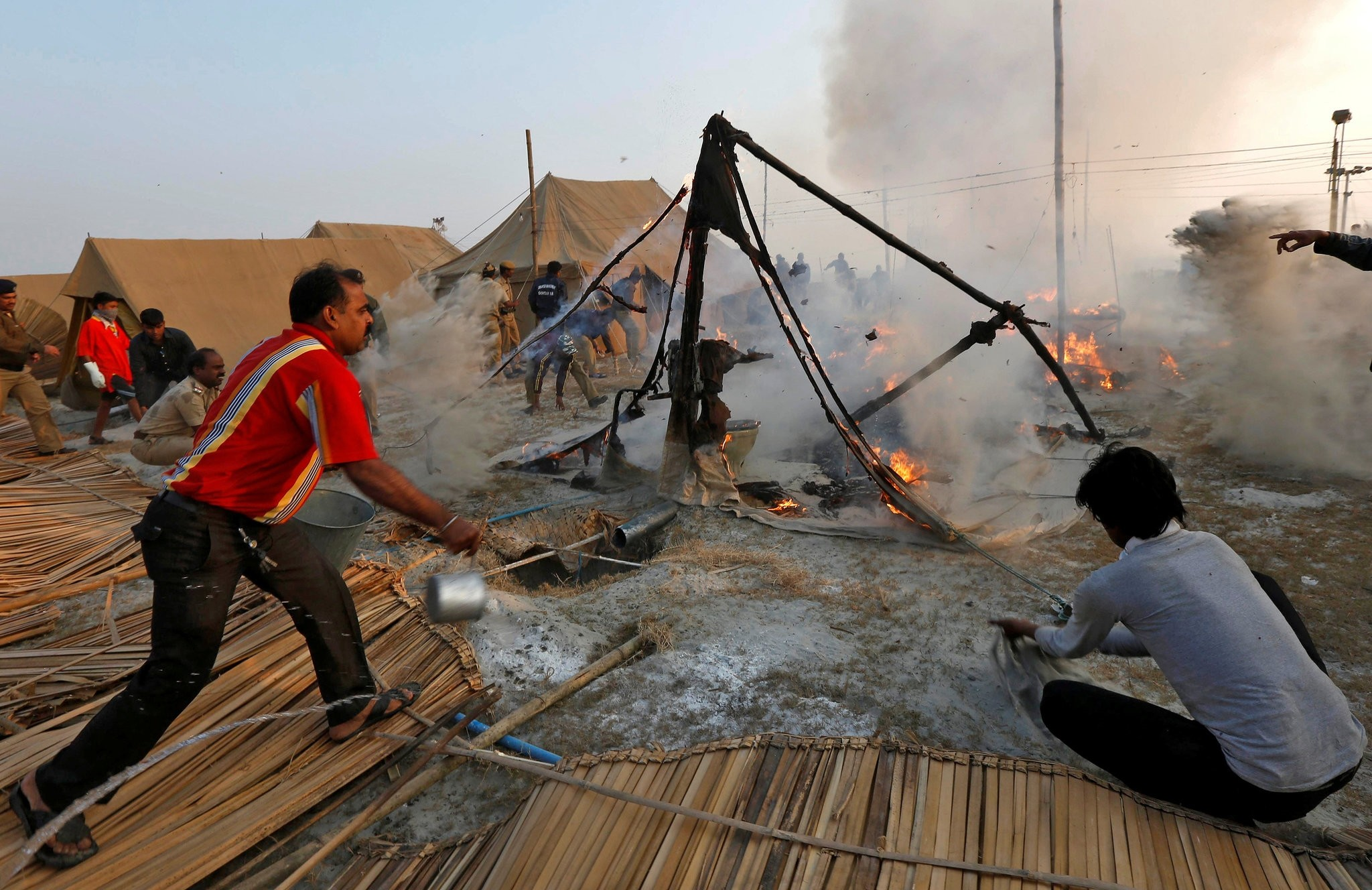 People throw water to extinguish fire that broke out in a tent on the banks of the river Ganges where hundreds of Hindu pilgrims had gathered for of ,Makar Sankranti, festival, in India. (REUTERS PHOTO)