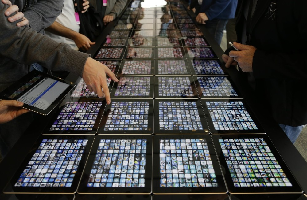 Developers look over new apps displayed on iPads at the Apple Worldwide Developers Conference in San Francisco.