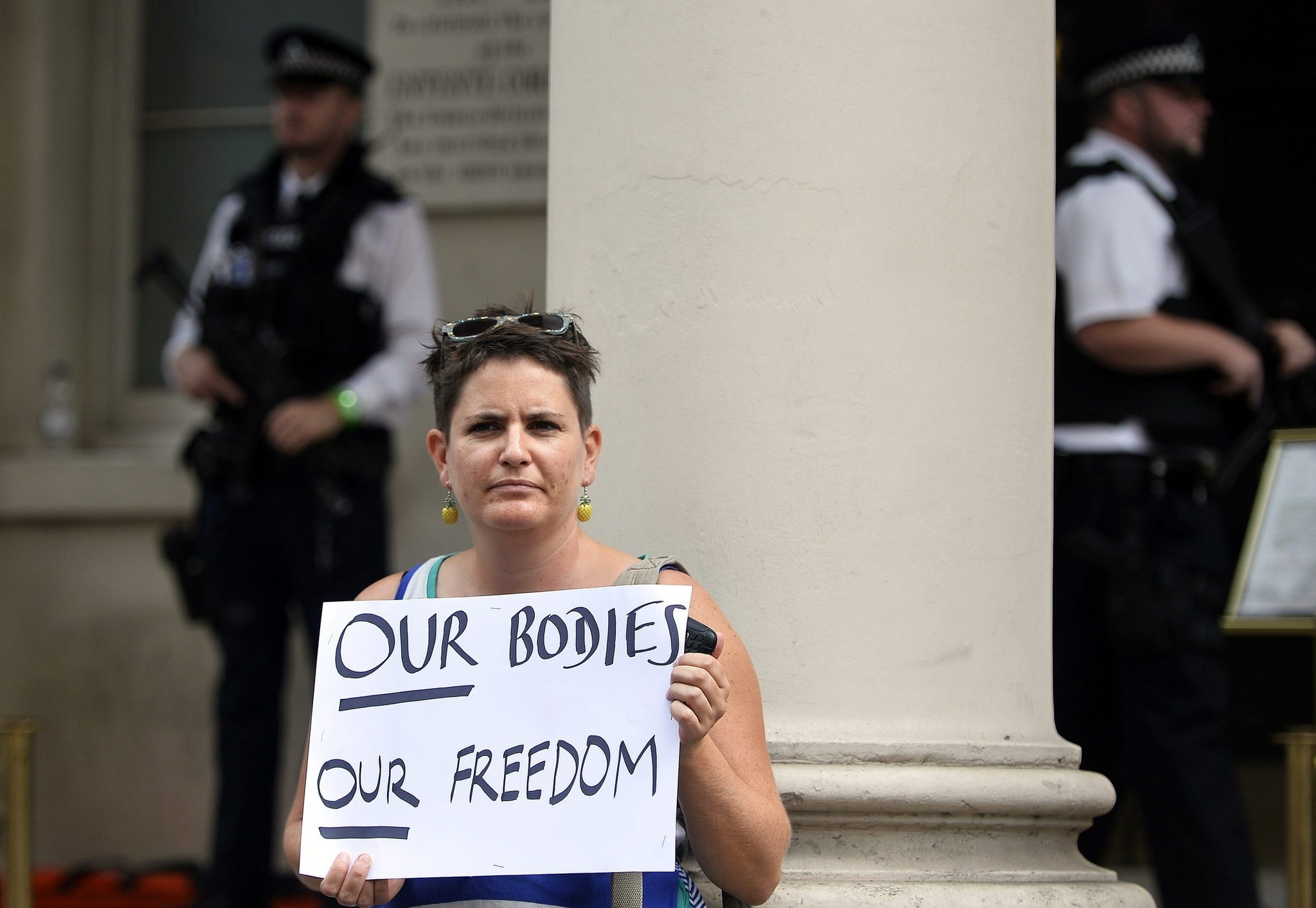 A woman holds a placard during a 'Wear what you want beach party' protest outside of the French Embassy in London, Britain, 25 August 2016. (EPA Photo)