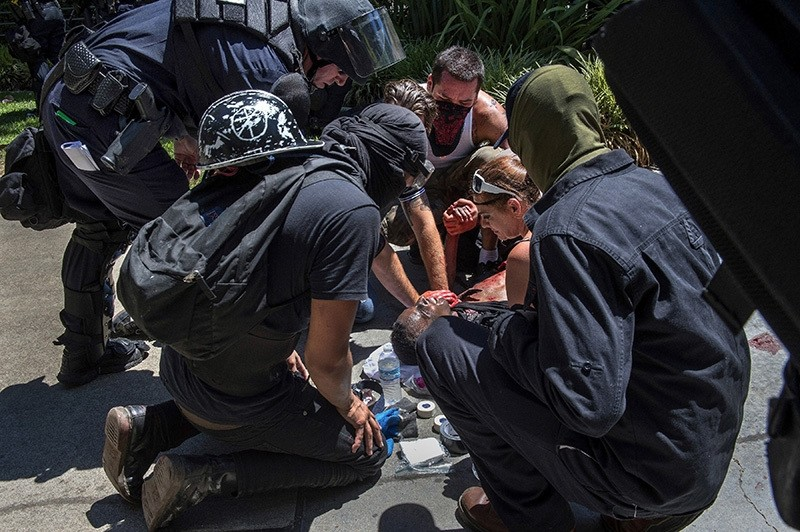 A victim is attended after he was stabbed during a rally at the State Capitol in Sacramento, Calif., on Sunday, June 26, 2016. (AP Photo)