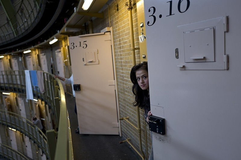 In this Saturday, May 7, 2016 photo, Afghan refugee Shazia Lutfi, 19, peeks through the door of her room at the former prison of De Koepel in Haarlem, Netherlands. (AP Photo)