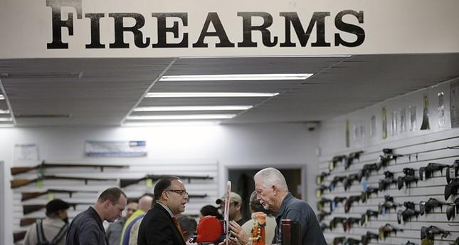 In this Dec. 9, 2015, file photo, sales associate Mike Conway, right, shows Paul Angulo guns at Bullseye Sport gun shop in Riverside, Calif. (AP Photo)