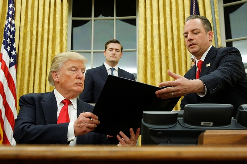 U.S. President Donald Trump hands Chief of Staff Reince Priebus (R) an executive order that directs agencies to ease the burden of Obamacare, after signing it in the Oval Office in Washington, U.S. on Jan. 20, 2017. (Reuters Photo)