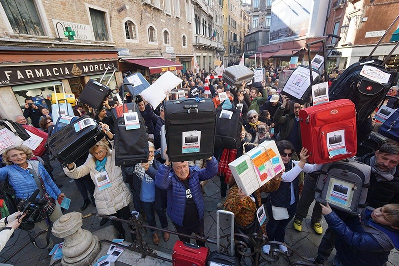 Residents of Venice hold luggages during the 'Venexodus' demonstrations in Venice, Italy, 12 November 2016.  (EPA Photo)