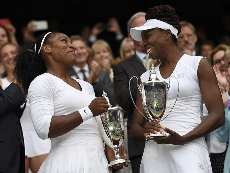 USA's Serena Williams and Venus Williams celebrate winning their womens doubles final against Hungary's Timea Babos and Kazakhstan's Yaroslava Shvedova with the trophies (Reuters Photo)