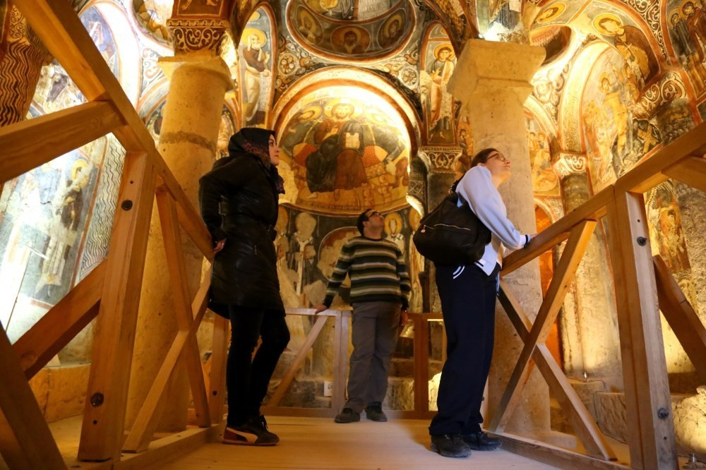 Tourists looking at the frescoes in a rock-cut church in Cappadocia.