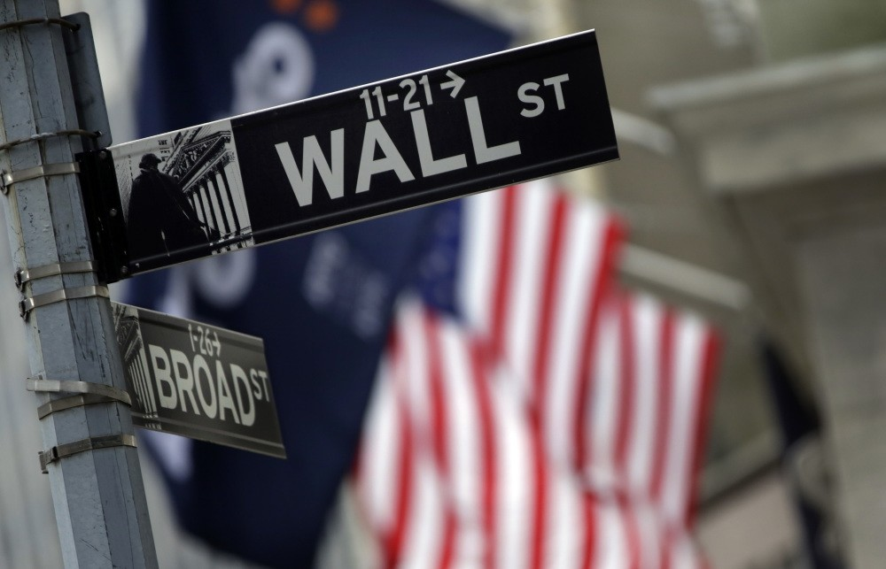 File photo, shows a Wall Street sign adjacent to the New York Stock Exchange. Key U.S. jobs data to be announced later in the week could help determine how soon the U.S. Federal Reserve raises interest rates.