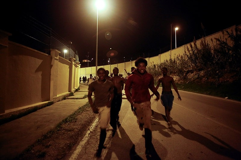 African migrants run on a road after crossing the border fence between Morocco and Spain's north African enclave of Ceuta, December 9, 2016. (Reuters Photo)