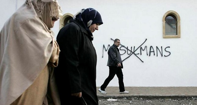 Muslim residents walk past racial slurs painted on the walls of a mosque in the town of Saint-Etienne, central France.