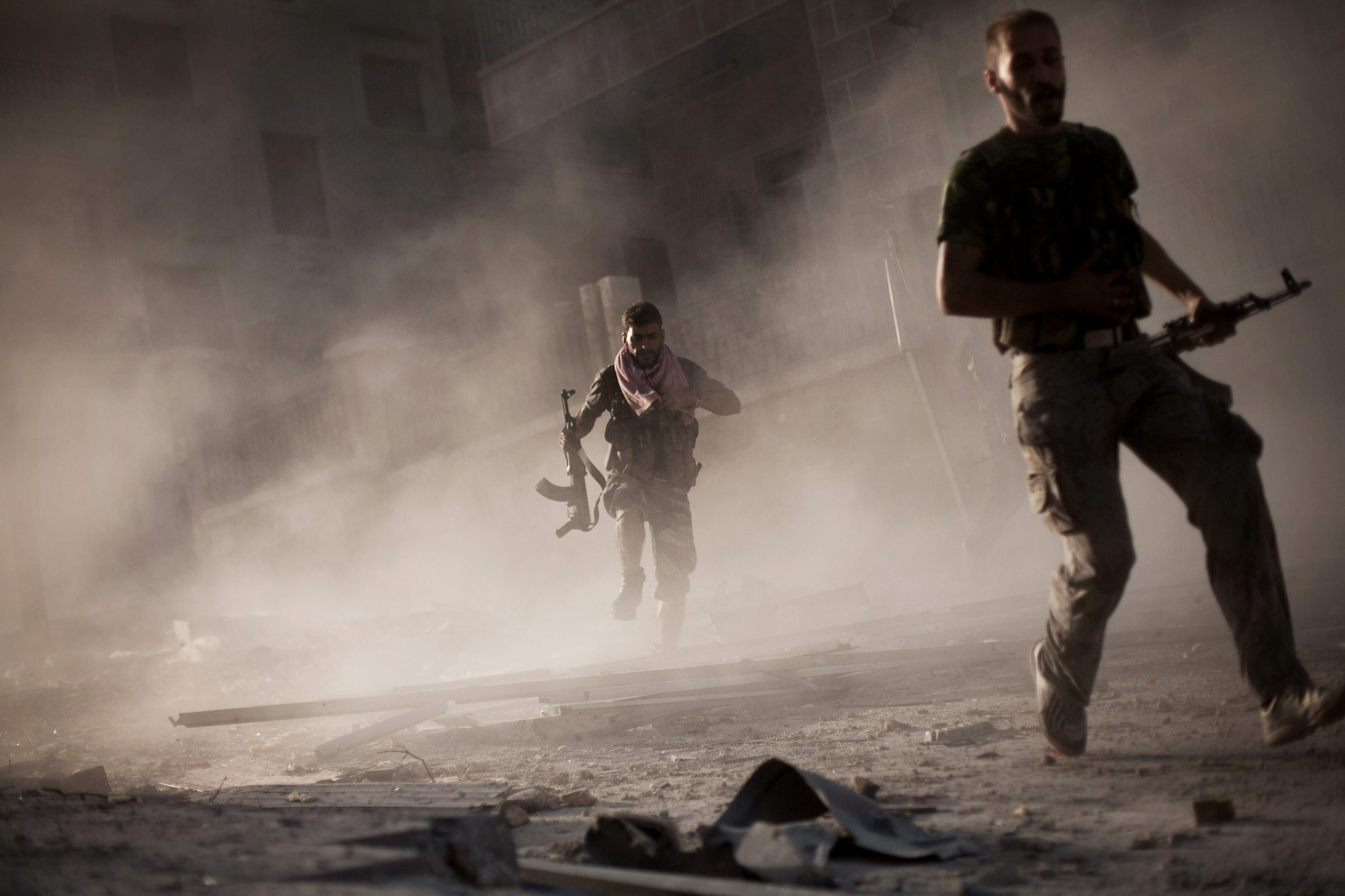Two rebel Free Syrian Army soldiers run after attacking a Syrian Army tank during fighting in the Izaa district in Aleppo, Syria. (AP Photo)
