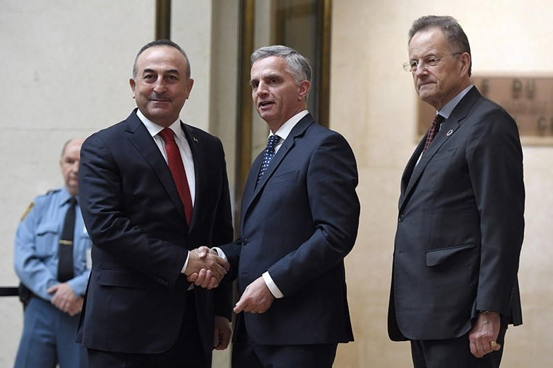 Turkish FM Mevlu00fct Cavuu015fou011flu, left, shakes hands with Swiss FM Didier Burkhalter, center, before the Conference on Cyprus at the European headquarters of the United Nations in Geneva, Switzerland, Thursday Jan. 12, 2017. (AP Photo)