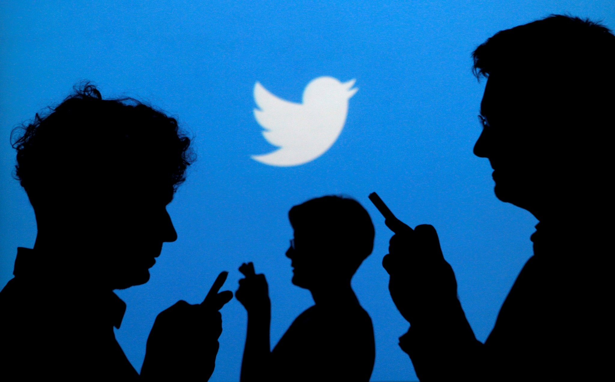 People holding mobile phones are silhouetted against a backdrop projected with the Twitter logo. (Reuters Photo)