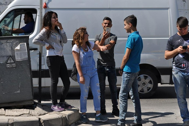 This June 12, 2016 photo shows several youngsters taking pictures in front of Izmir Police Department building in Bozyaka district. (DHA Photo)