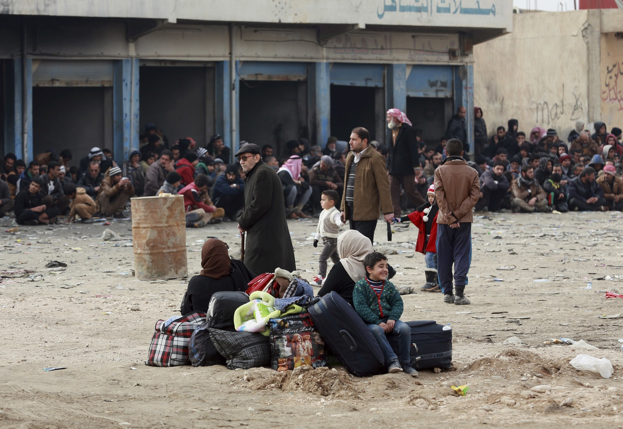 Iraqis waiting at the gathering point to be taken for a camp for internally displaced people, in Bartella, Dec 31, 2016. (AP Photo)