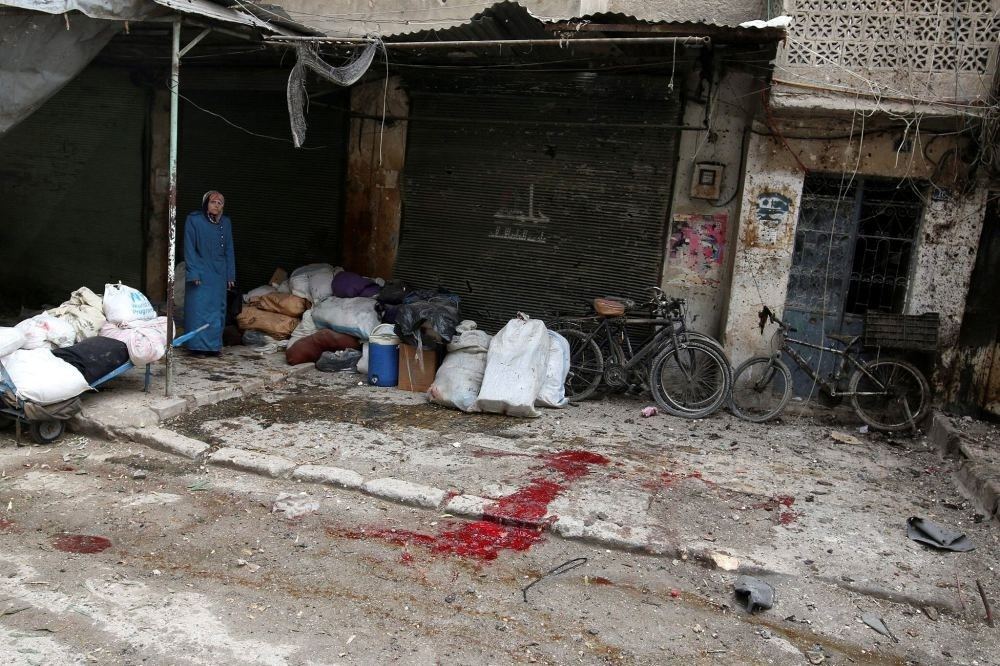 A woman stands near the blood-stained ground after strikes on opposition-held besieged al-Zebdieh district, in Aleppo, Syria, Dec. 5.