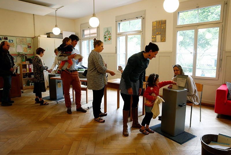 People cast their ballots during a vote on whether to give every adult citizen a basic guaranteed monthly income of 2,500 Swiss francs ($2,560), in a school in Bern, Switzerland. (Reuters Photo)