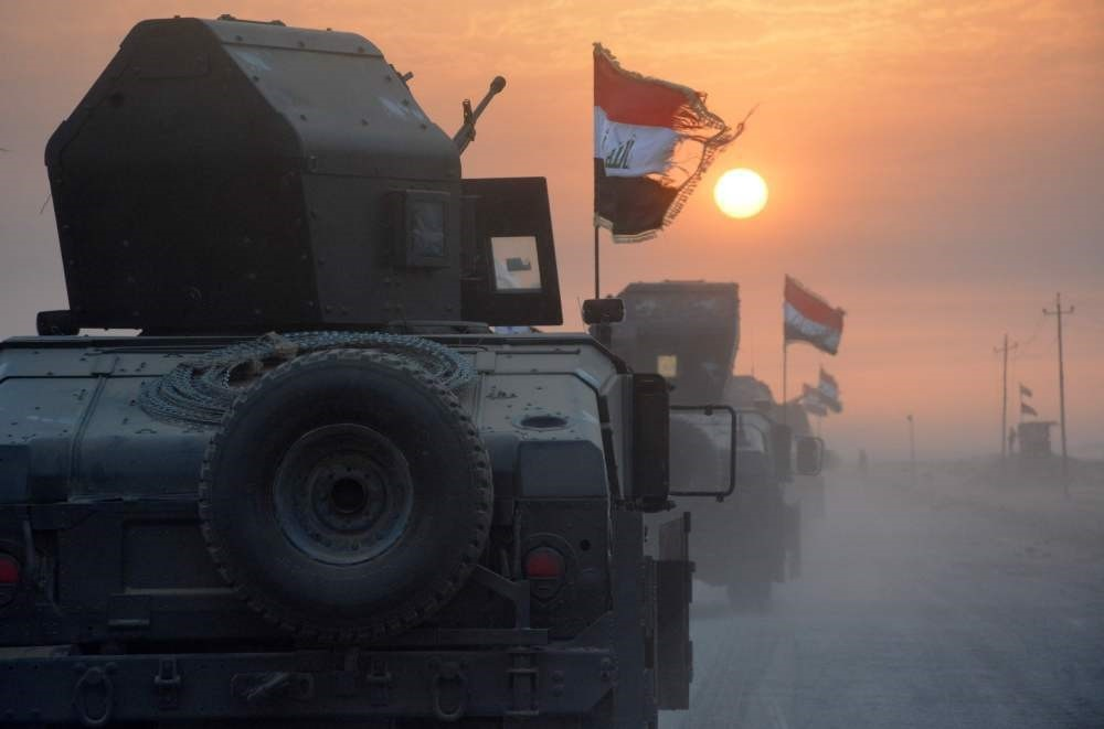 Pro-government forces drive in military vehicles in Iraq's eastern Salaheddin province, south of Hawijah, on Oct. 10, 2016.