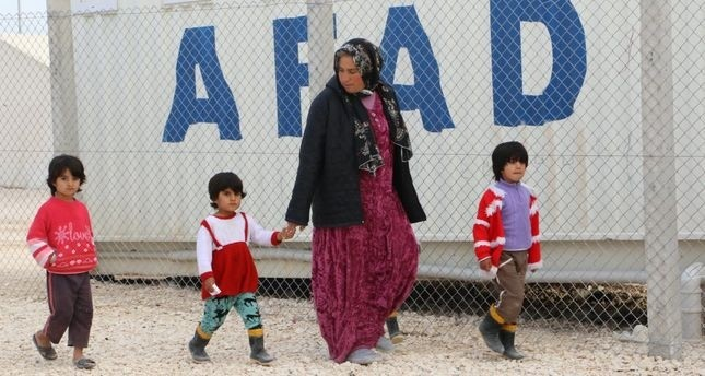 A Syrian refugee woman walks with children at a refugee camp in u015eanlu0131urfa. Women and children make up three quarters of the refugee population according to UNHCR.