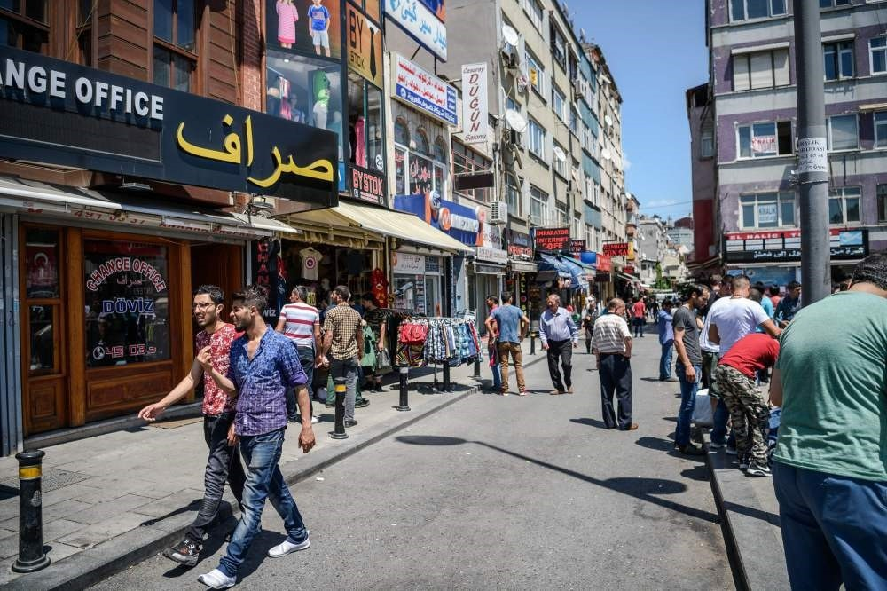 Syrian and Turkish people walk in a street next to shops with Arabic letters in Fatih in Istanbul. (AFP Photo)