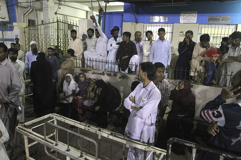 People gather outside an emergency ward of a local hospital after hearing news of a bomb blast at a shrine, in Karachi, Pakistan, Saturday, Nov. 12, 2016. (AP Photo)