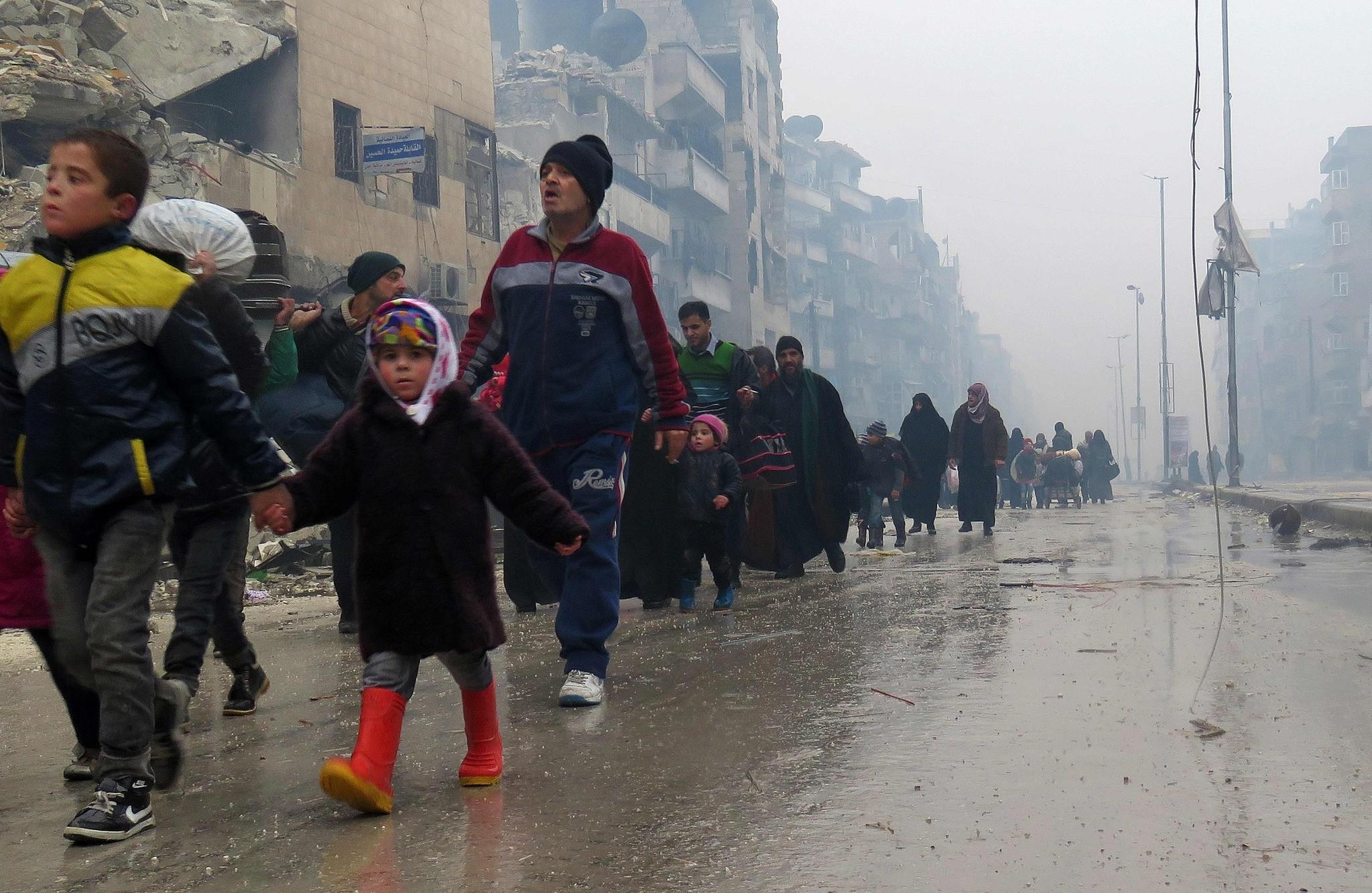 Syrian residents, fleeing violence in the restive Bustan al-Qasr neighbourhood, arrive in Aleppo's Fardos neighbourhood on Dec. 13.