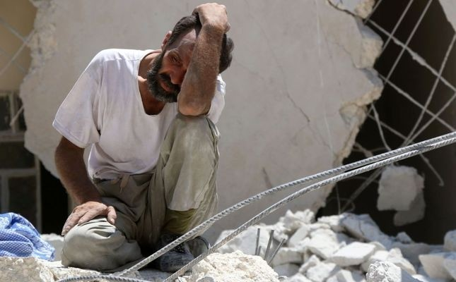 A man looks on as Syrian civil defense workers look for survivors under the rubble of a collapsed building following reported airstrikes on July 17 in the opposition-controlled neighborhood of Karm Homad in the northern city of Aleppo.