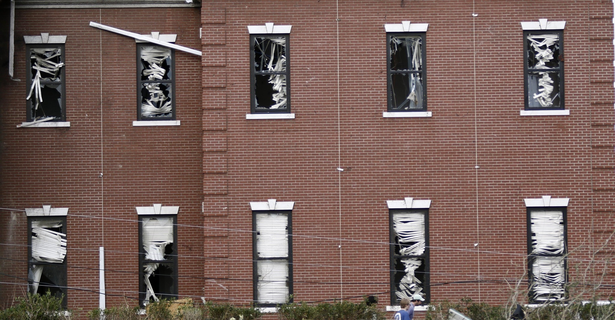 The damaged blinds in the windows of William Carey University's School of Business are seen in Hattiesburg, Miss., Saturday, Jan. 21, 2017. (AP Photo)