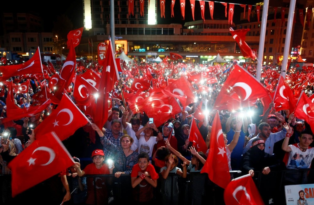 People wave flags as they listen to President Erdou011fan on a giant screen in Istanbul's Taksim Square, Aug. 10.