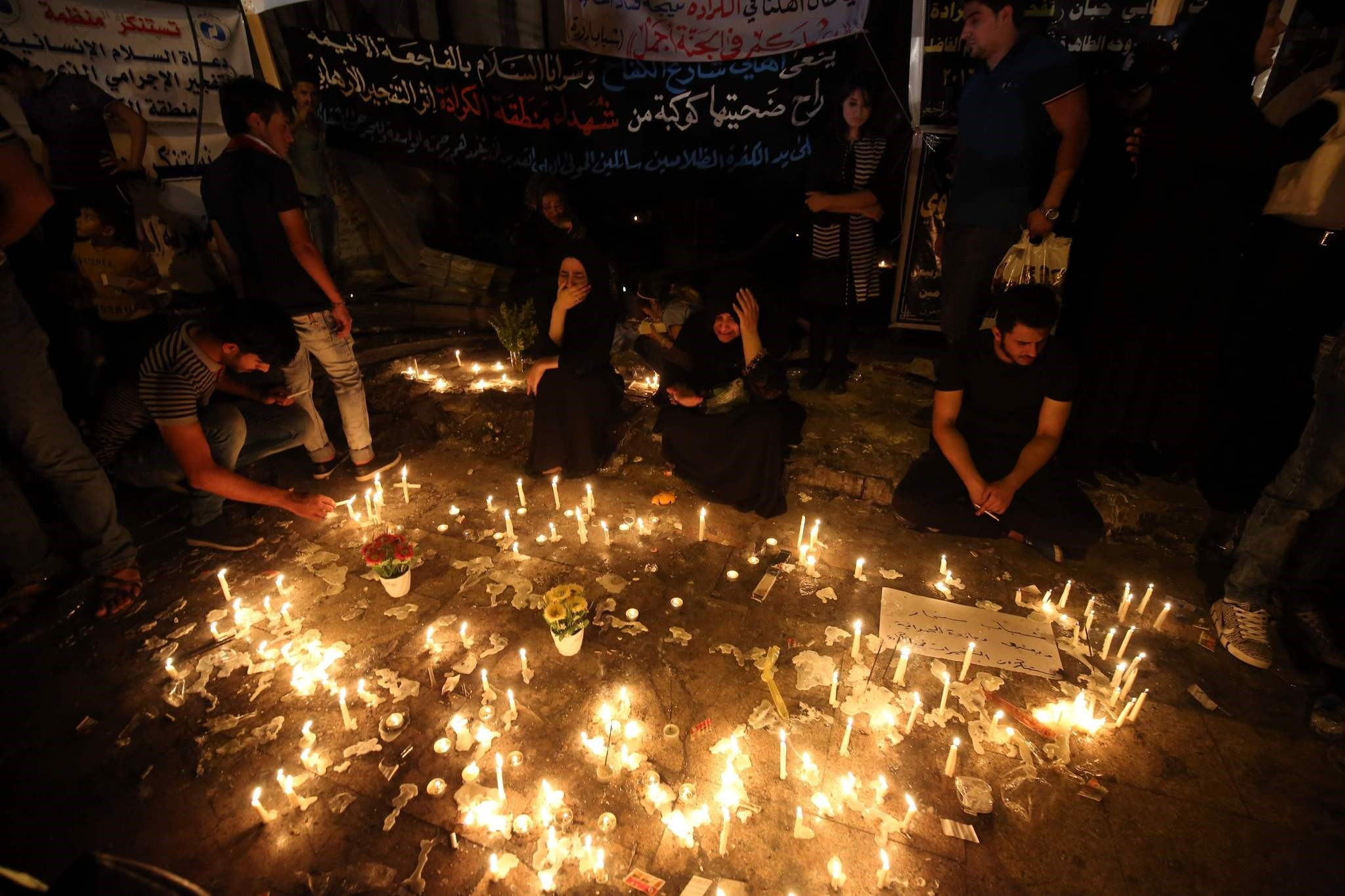 Iraqis light candles on July 5, 2016 at the site of a suicide car bomb attack which took place early on July 3 in Baghdad's Karrada neighbourhood killing at least 213 people and wounding more than 200. (AFP Photo)