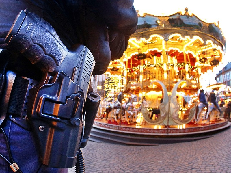 A German police officer stands next to a merry-go-round in the Christmas market in Frankfurt, Germany, Tuesday, Dec. 20, 2016 (AP Photo)