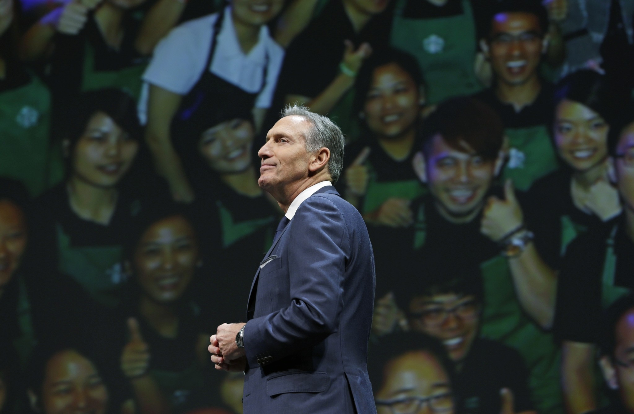 Starbucks CEO Howard Schultz walks in front of a photo of Starbucks baristas, at the coffee company's annual shareholders meeting in Seattle. (AP Photo)