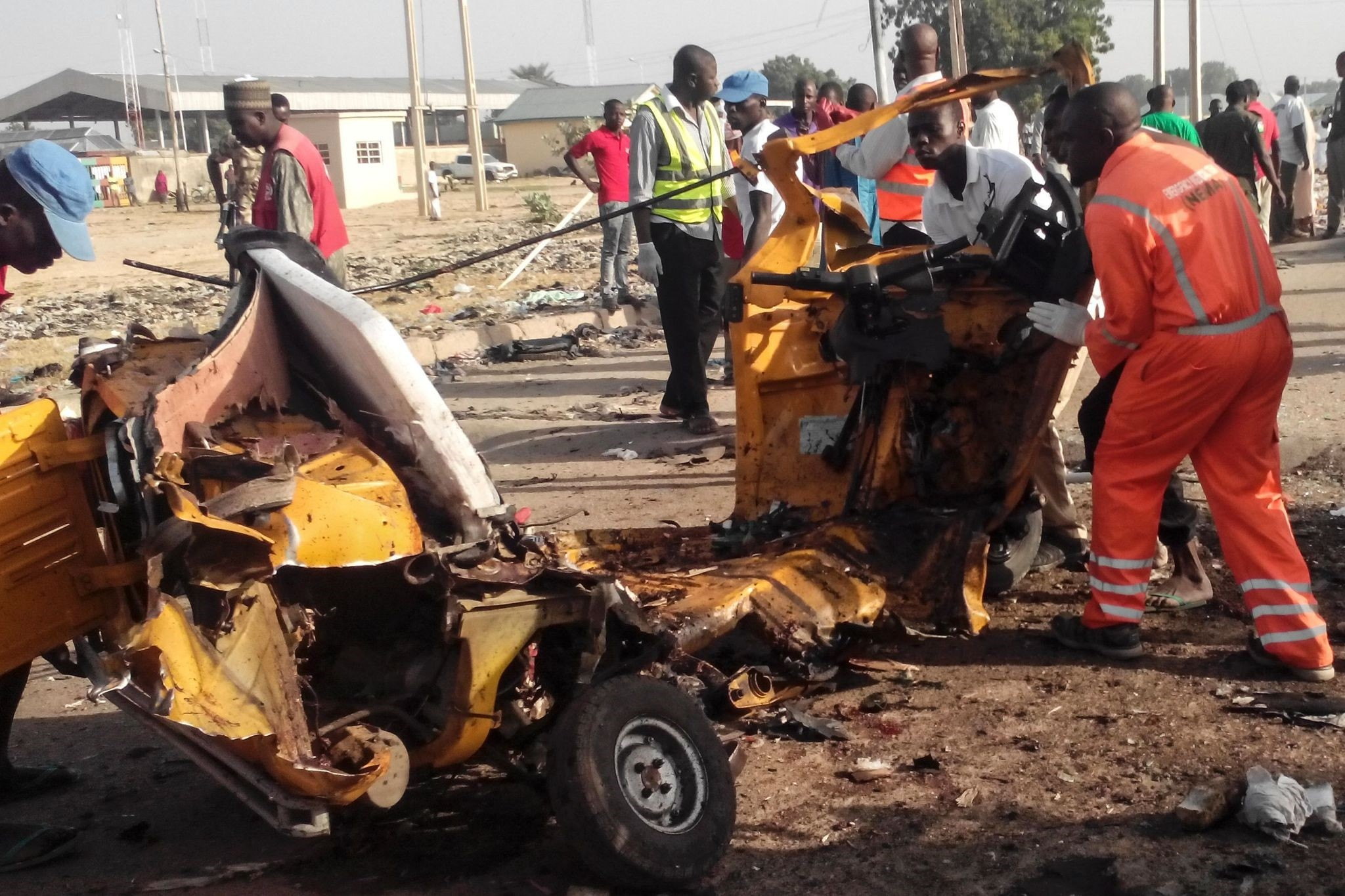 This file photo taken on October 29, 2016 shows emergency personnel standing near the wreacked remains of a vehicle ripped apart following two suicide bombings in Nigeria. (AFP Photo)