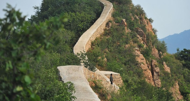 This picture taken on September 21, 2016 shows a villager walking on a paved-over section of the Great Wall of China at Suizhong, in China's northeast Liaoning province. (AFP Photo)