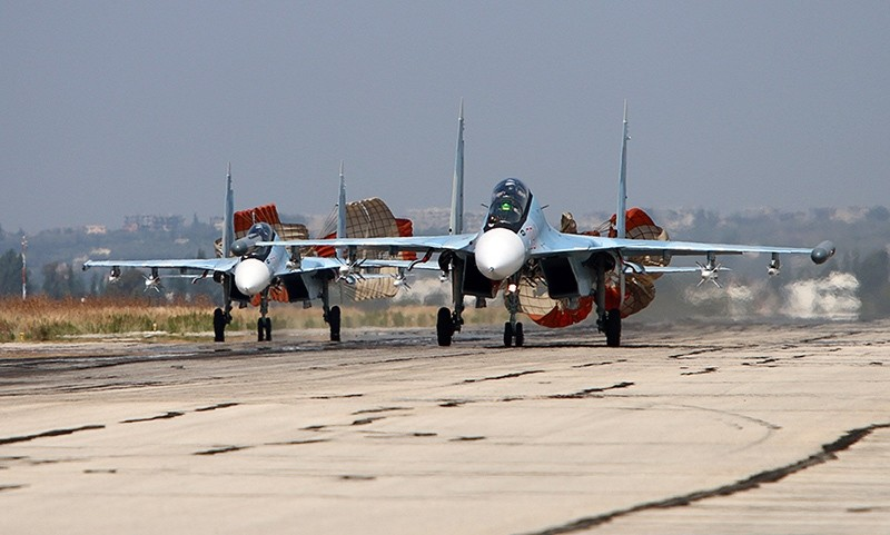 picture taken on October 3, 2015 shows Russian Sukhoi SU-30 SM jet fighters landing on a runway at the Hmeimim airbase in the Syrian province of Latakia. (AFP Photo)