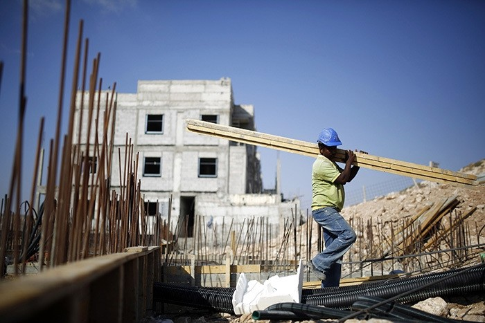 A labourer works on a construction site in Pisgat Zeev, an urban settlement in an area Israel annexed to Jerusalem after capturing it in the 1967 Middle East war August 12, 2013. (Reuters Photo)