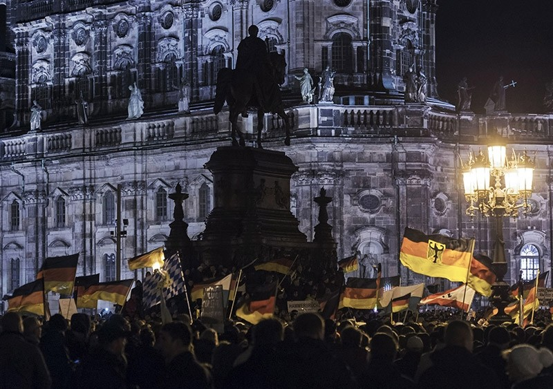 In this file photo dated Dec. 22, 2014, participants of an anti-migrant rally wave German flags. (AP Photo)