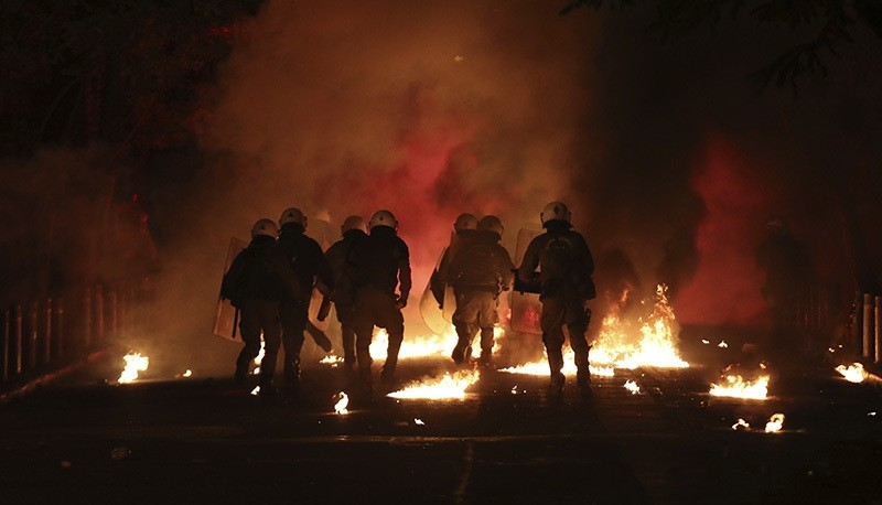 Riot police try to avoid petrol bombs and flares thrown by protesters during clashes in Athens, on Tuesday, Dec. 6, 2016 (AP Photo)